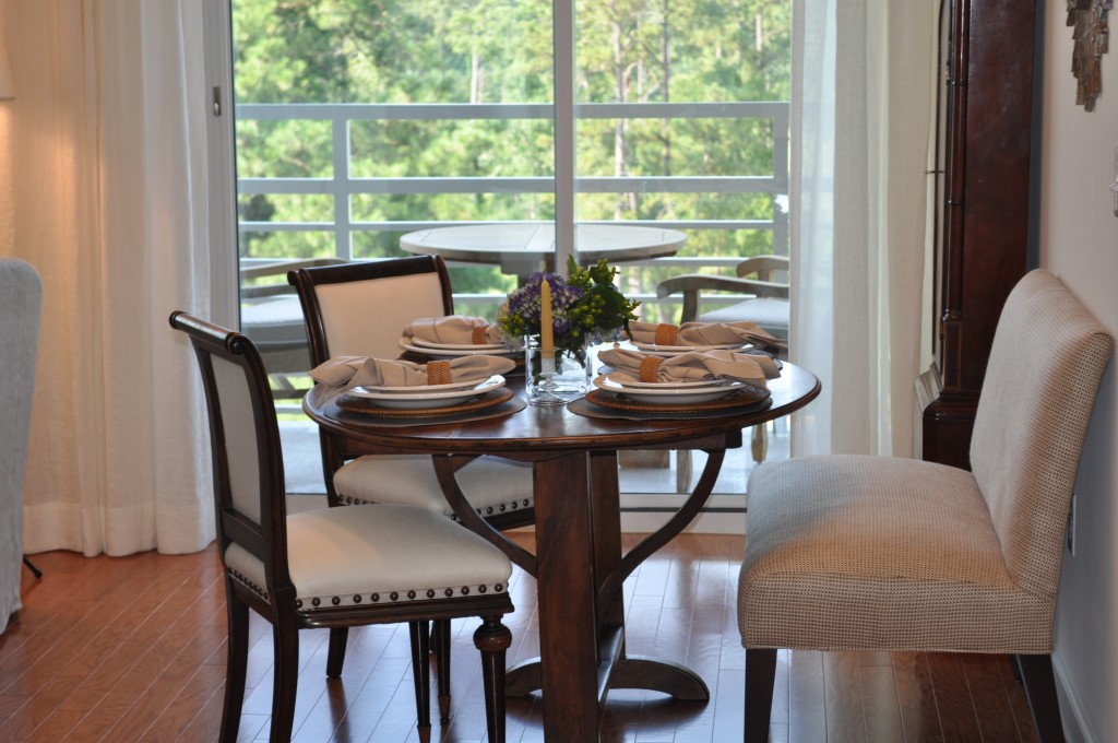 "Dining area: In order to maximize the small dining space, I decided to use a dual seat banquette.  I was so excited when I found this antique french winetasting table with perfect proportions. When I purchased the antique french chairs, they were upholstered in a brown leather.  I had them reupholstered in a cream linen with a flax trim/large nailheads.  The new fabric and detailing really makes them ""pop""!"